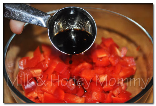 drizzling balsamic vinegar on red bell peppers